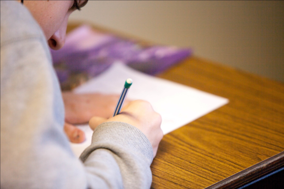 A student acing the ACT while sitting at a table.