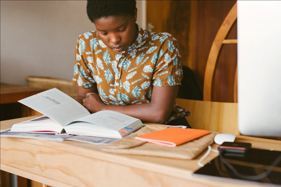 image of a woman reading a book at her desk